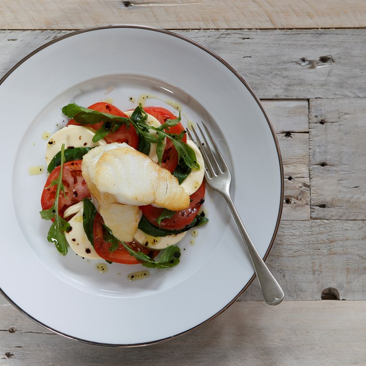 Pan-fried cod on a bed of mozzarella-tomato salad